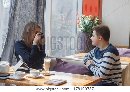 Cheerful couple dating in a cafe. They are having fun and smiling making pictures from retro photo camera. They are looking at each other.