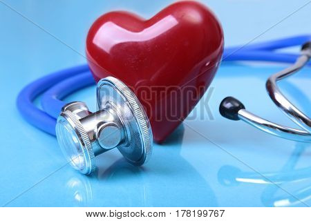 Medical stethoscope and red heart isolated on blue mirror background. you can place your text