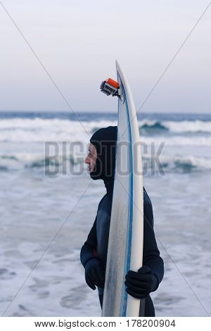 Wet athletic surfer with surfboard after riding. He wears a wetsuit or waterproof suit