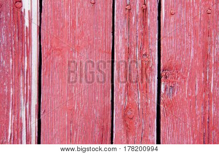 Texture of boards with exfoliating old crimson paint.