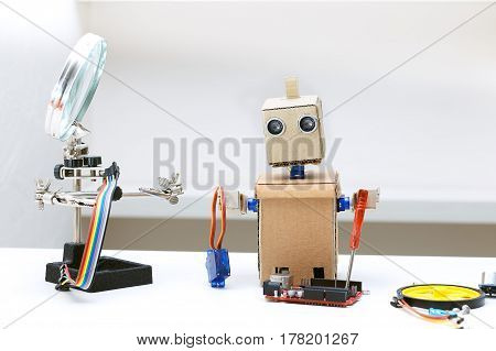 Robot with hands and other parts for assembling the robot are on the table