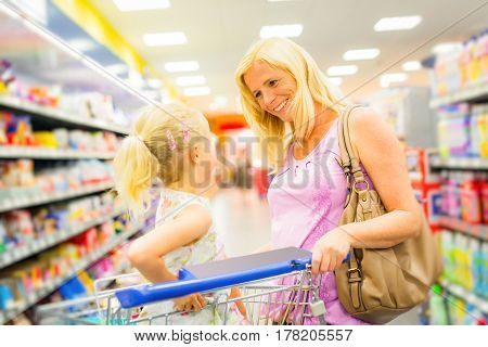 mother and daughter at the supermarket shopping for groceries