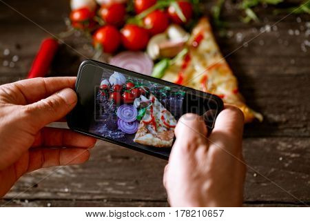 man using smartphone to take picture of slice of pizza on wooden table
