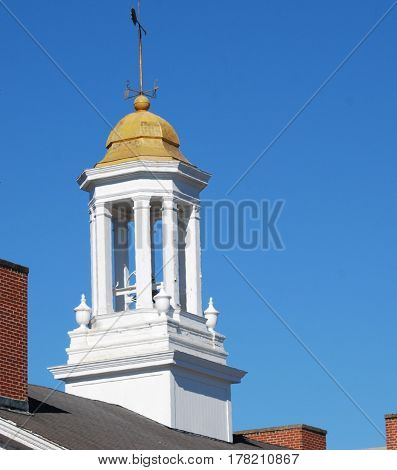 White decorative cupola with gold tin roof sits on roof underneath a deep blue sky