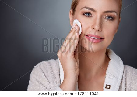 nourished middle aged woman cleaning her perfect skin  with cotton pad
