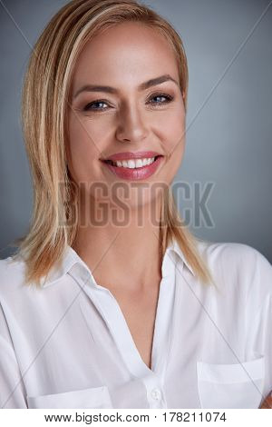 Attractive middle-aged blond woman standing and smiling while looking  directly at the camera