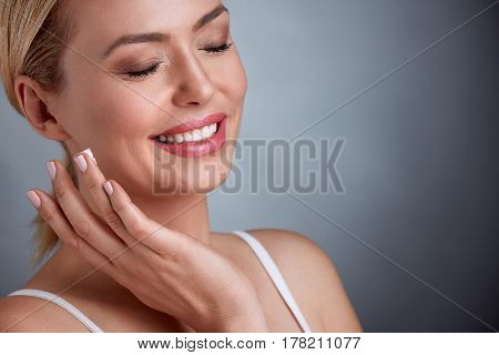 Middle aged woman enjoying in face cream, health and beauty cream