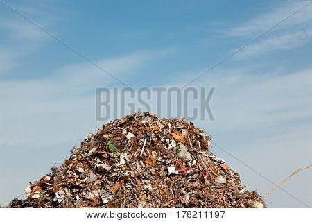 a huge pile of scrap metal is rising towards the sky