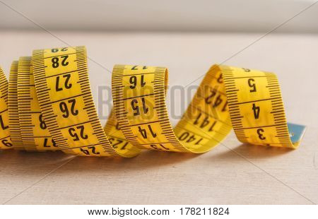 Curved measuring tape. Measuring tape of the tailor. Closeup view of yellow measuring tape