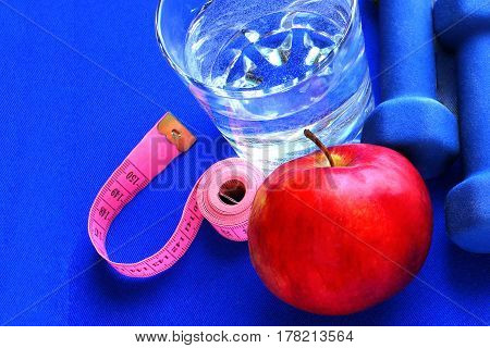 Close up of a pristine red apple two dumbbells  and glass water, blue atheletic small rug of   with reflection , sound lifestyle