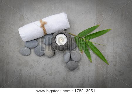 Gray stones in bowl with bamboo leaf,towel, candle -gray background