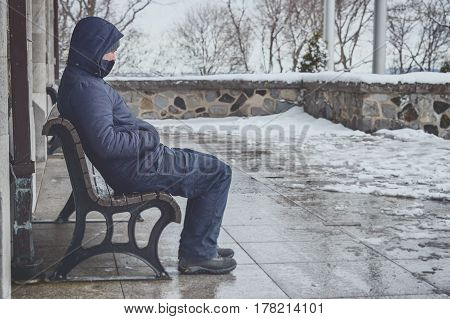 Man Sitting On Bench In Winter With Snow On The Ground