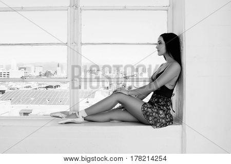 Classical ballet dancer portrait at window background.