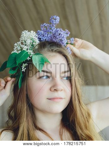 white caucasian blonde girl put wreath with white and purple lilac on her head