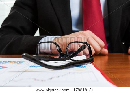Detail of a pair of eyeglasses on a business report