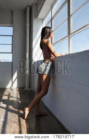 Beautiful sexy young woman is looking out of the window