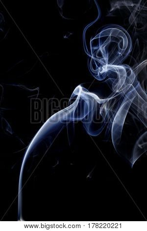 Abstract art. Color white blue smoke from the aromatic sticks on a black background. Background for Halloween. Texture fog. Design element. The concept of aromatherapy.