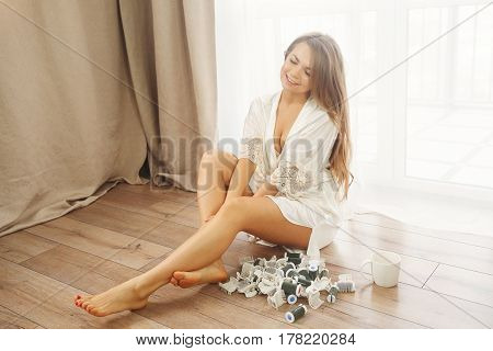 Sweet Young housewife sitting on the floor near the window. Girl in bathrobe removed the curlers. Good morning.