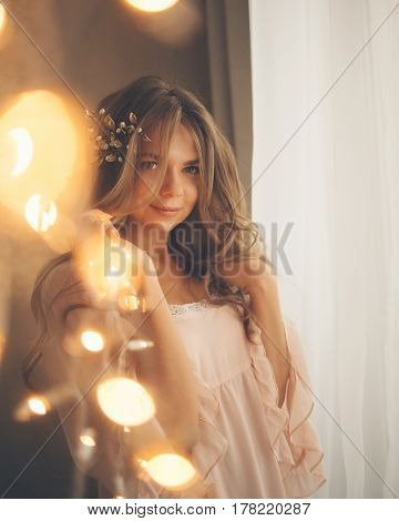 Young cute housewife with a garland. Girl in sexy gown. Good morning. Dreamy eyes. Soft focus. Toning. Creative bokeh.