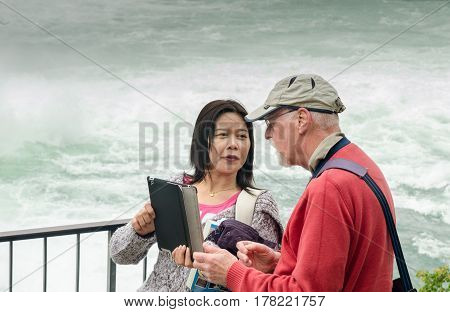 Young Asian Girl And Elderly Tourist Do Selfie By Tablet At Rhine Falls, The Largest Plain Waterfall