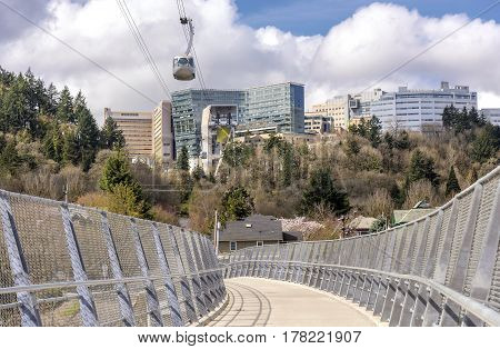 Aerial tram transporting people over a pedestrian overpass Portland Oregon.