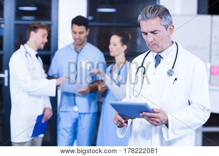 Doctor using tablet and colleagues discussing in background
