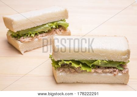 Two tuna sandwiches on a wooden table