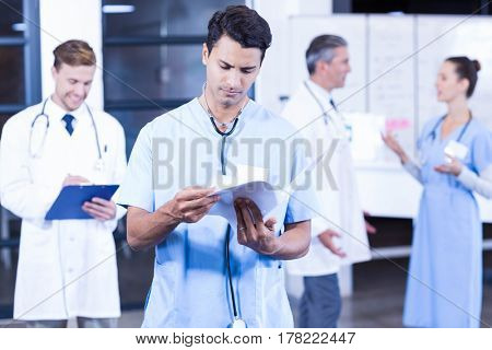Doctor checking medical report while his colleagues discussing in background