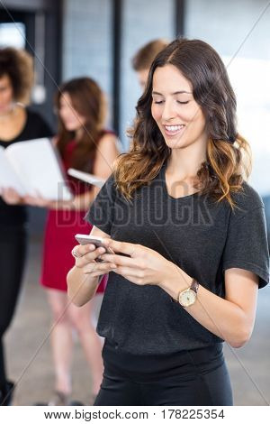 Businesswoman text messaging on smartphone while her colleagues standing behind her in office