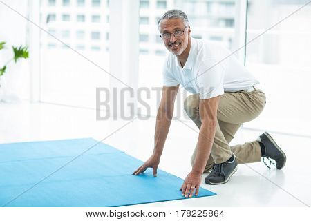 Portrait of physiotherapist laying exercise mat at home