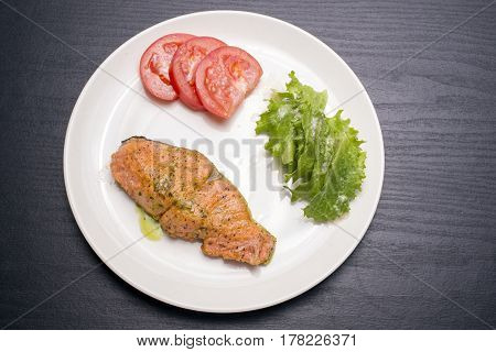 Meuniere salmon with raw vegetables on white plate