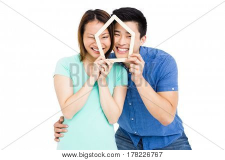 Young couple holding house shaped popsicle sticks on white background