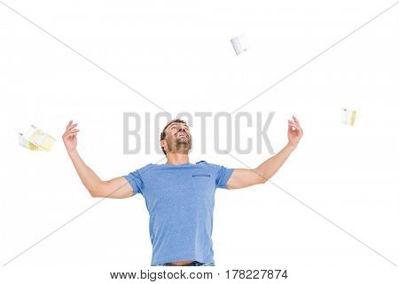 Young man throwing currency notes in excitement on white background