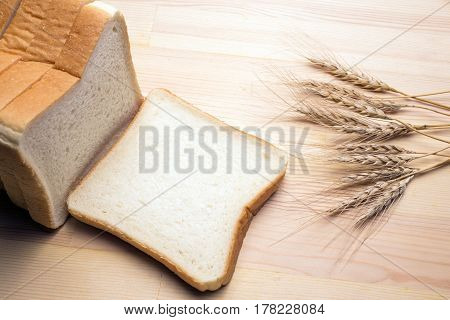 Cut bread and wheat ears on a wooden table