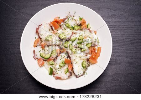 Octopus with vegetables carpaccio on a white dish