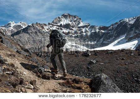 Mountain Climber with Backpack and walking Poles walking up along rocky Ridge toward high Altitude snowy Peak