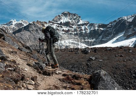 Athlete with Backpack and walking Poles walking up along rocky Ridge toward high Altitude snowy Mountain