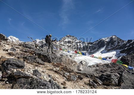 High Altitude Mountain Landscape and Alpine Climber taking Picture on Mobile Telephone staying on rocky Edge along Nepalese Flags