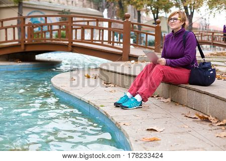 Inspired Woman in casual and sporty Clothing sitting in Park next to Pond and using tablet pc device