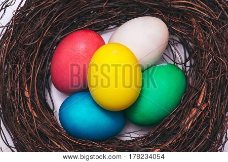 Easter eggs in nest on marble background.