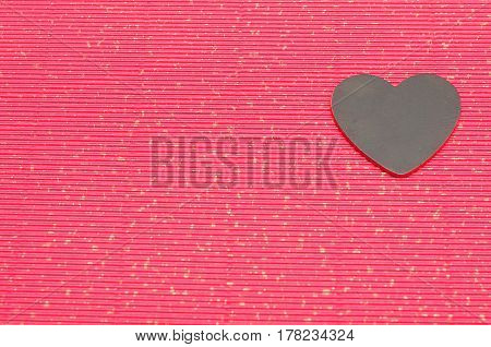A black heart isolated on a red background