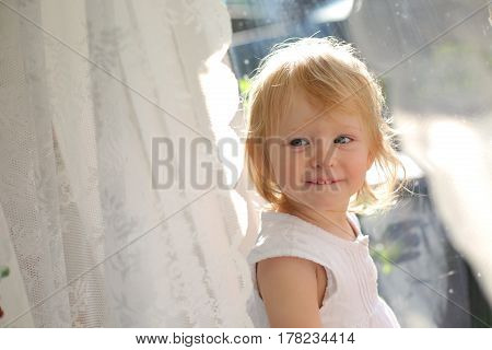 Baby girl looking through the window. Toddler's fantasy and dreams. Sad little girl looking out the window