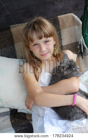 Happy little girl with a cat outdoors sitting and hugging a pet
