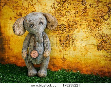 Plush toy elephant on background of world map