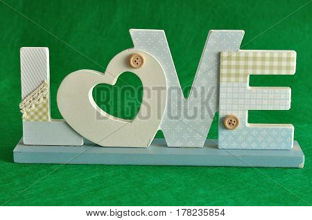 Valentine's Day. Love in blue letters isolated on a green background