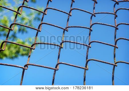 iron chain link fence against the blue sky. Soft selective focus and shallow depth of field