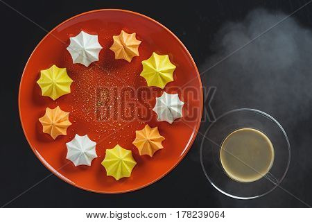 Multi-colored figured cookies on a round ceramic orange plate and a cup of hot coffee on a black background