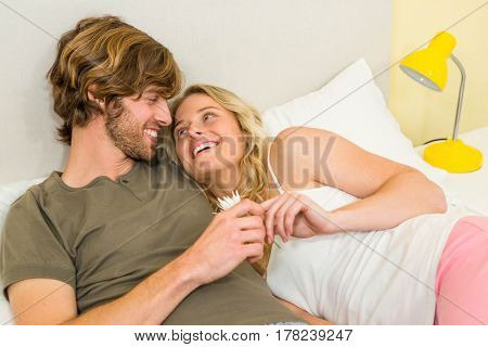Cute couple cuddling on their bed in the bedroom