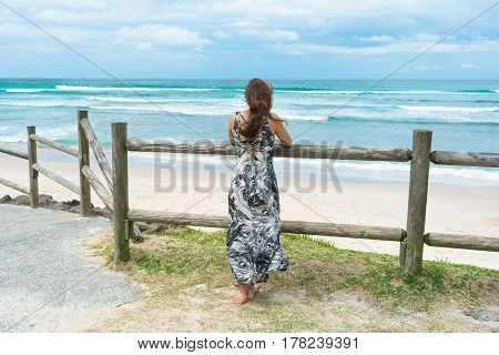 The woman with long dark hair wearing long romantic dress facing on the ocean is looking into the distance on the stormy ocean