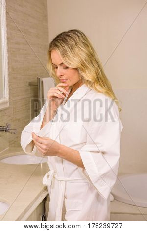 Pretty blonde woman holding a pregnancy test in the bathroom